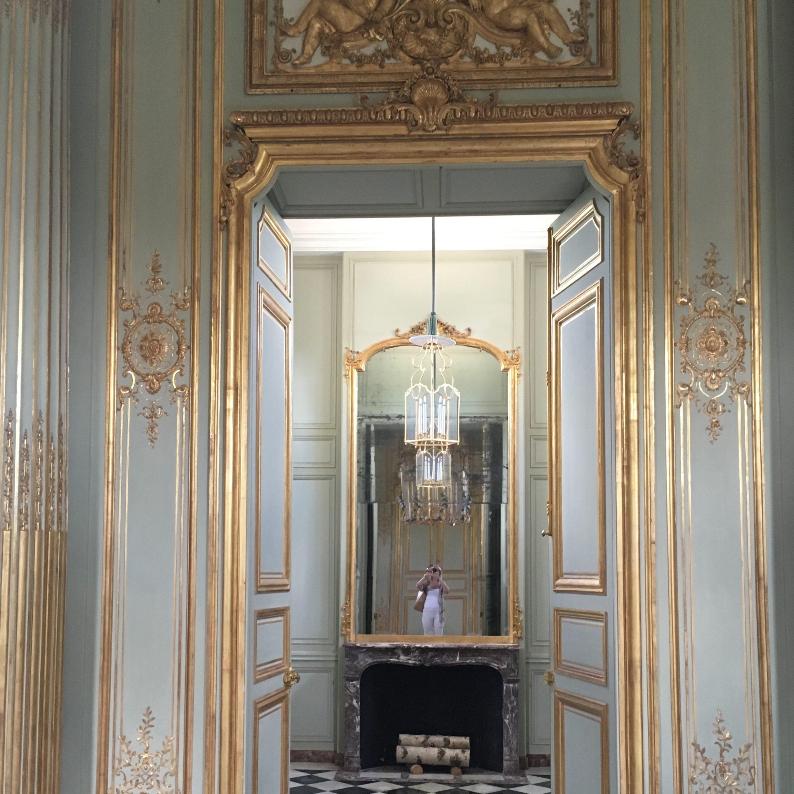 A beautiful mirror seen through a gilded doorway