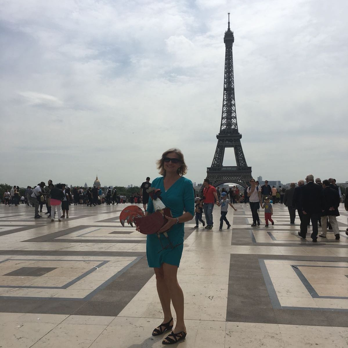 A woman holding a rooster in front of the Eiffel Tower